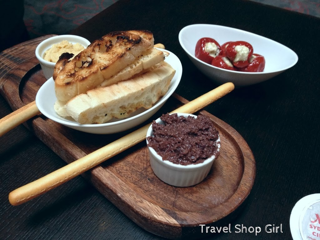 Crisp bread and Grissini sticks with hummus and olive tapenade, marinated peppers stuffed with feta