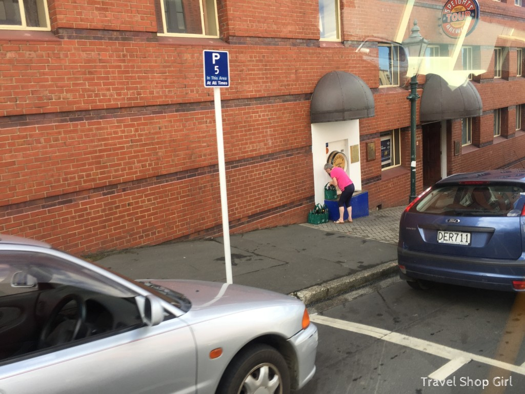 Woman collecting water in bottles outside of Speight's Brewery in Dunedin